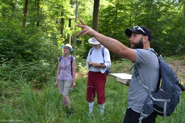 Randonneurs à la découverte de la forêt, suivant les explications de Romain CANTAT, animateur nature à la Maison de l'eau et de la rivière.
