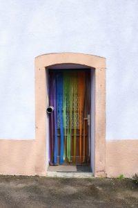 Porte extérieure, décorée de rubans aux couleurs de l'arc en ciel. A Dehlingen. Photo de François Génot.
