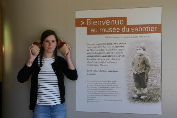 Jeune fille tenant une paire de sabot, à côté de l'affiche de bienvenue du Musée du Sabotier.