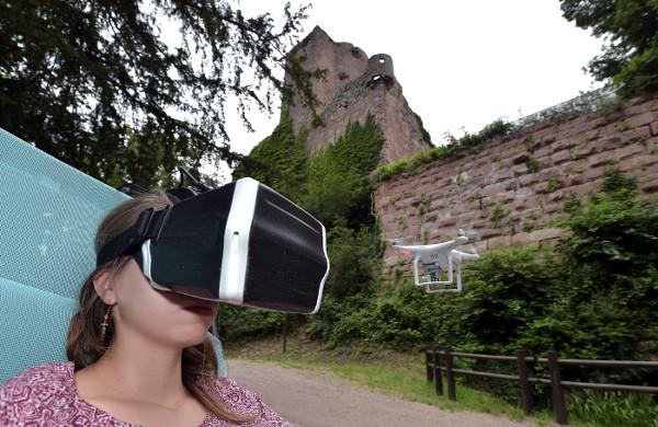 Jeune fille portant un casque de réalité virtuelle pour découvrir le château de Fleckenstein, grâce à un drone.