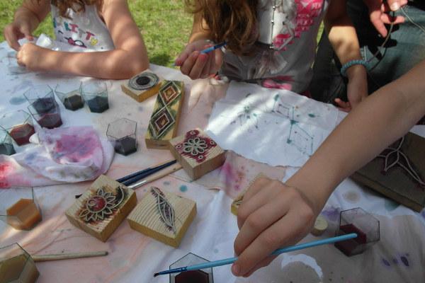Enfants dessinant des motifs floraux, à l'aide de tampons et d'aquarelle.