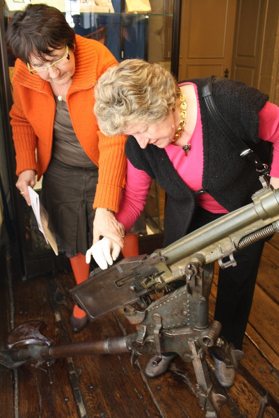 Guide accompagnant la découverte tactile d'un objet du Musée militaire et Erckmann-Chatrian de Phalsbourg par une personne non-voyante.