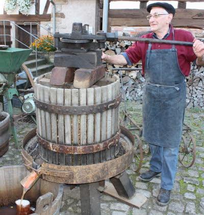 Bénévole de la Maison Rurale de l'Outre Forêt, actionnant un pressoir à jus.