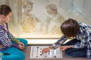 Deux enfants jouant à la marelle romaine.