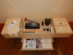 Kit à toucher du musée du pétrole, contenant des gants, une loupe, des plans et images thermo gonflés, des échantillons de pétrole ainsi qu'un modèle réduit de puit de pétrole.