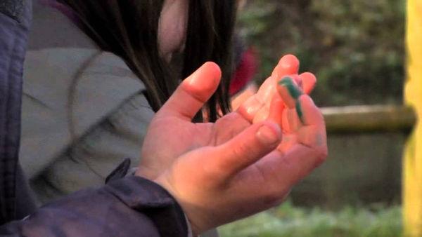 Participant à un atelier, recueillant l'eau de la rivière au creux de ses mains.