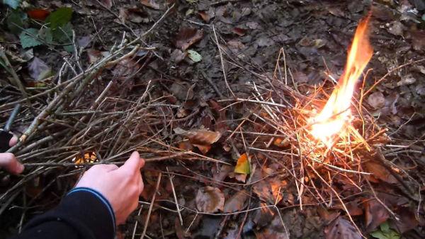 Une personne commence à allumer un petit feu en nature
