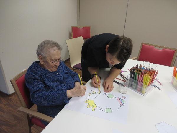 Une dame âgée et un enfant dessinent ensemble