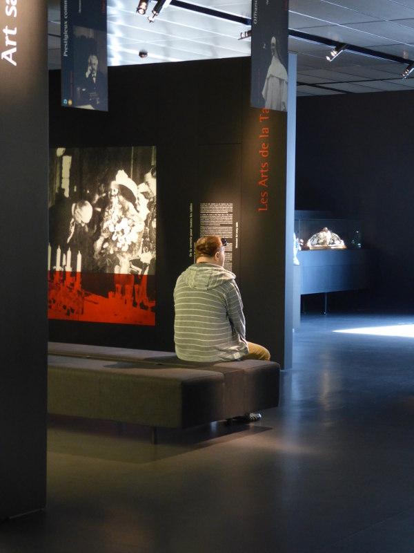 Un homme assis observe les collections du Musée Lalique