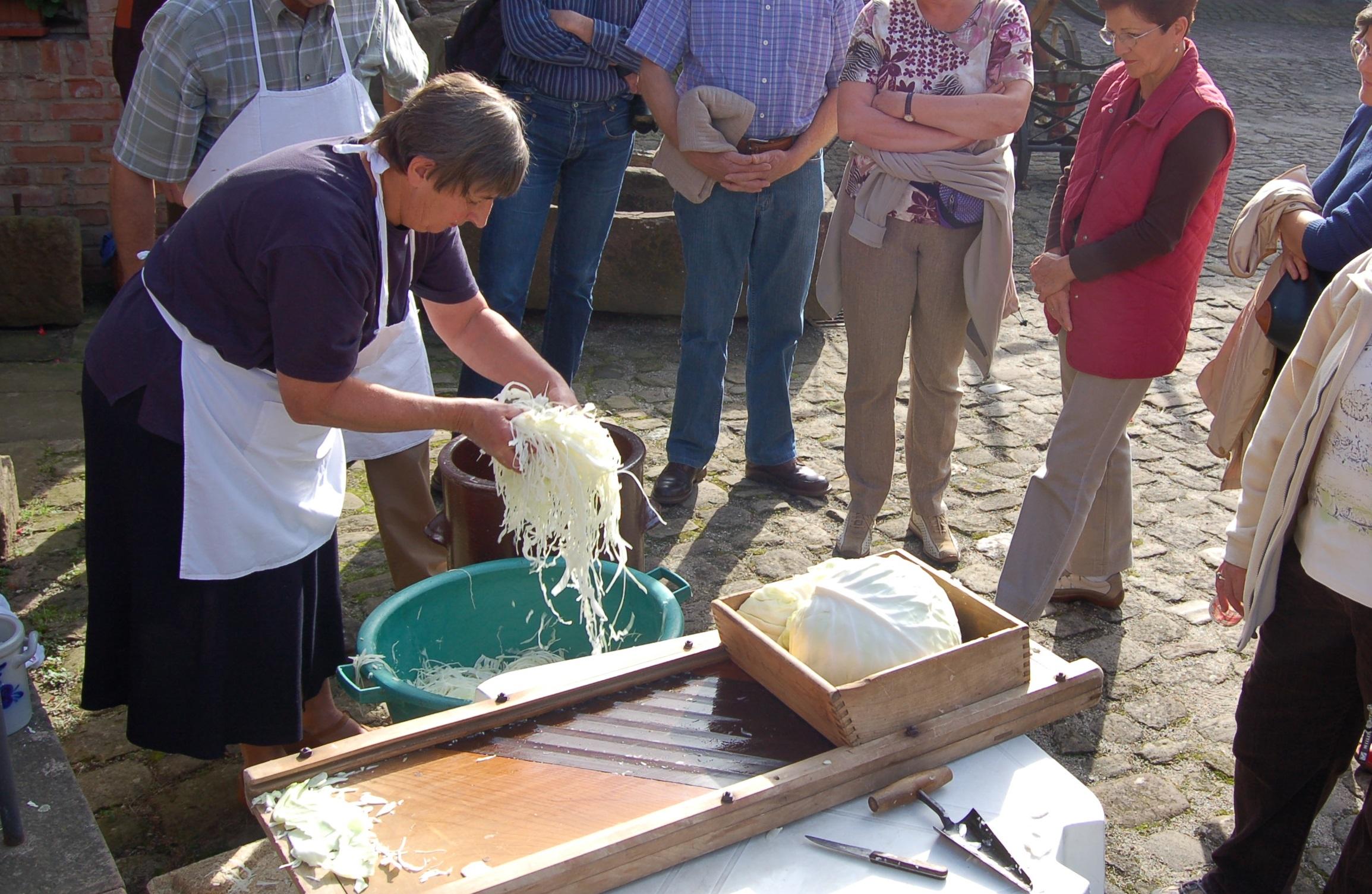 Bénévole de la Maison rurale de l'Outre Forêt, en pleine activité de débitage du chou à choucroute.